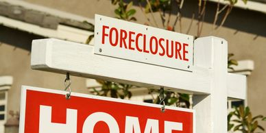 House with foreclosure sign on lawn